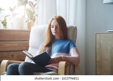portrait d'une jolie jeune fille aux cheveux rouges assise sur une chaise confortable lisant un livre