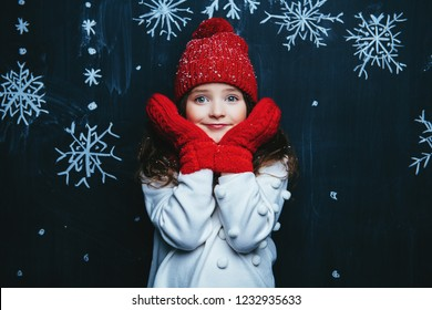 A portrait of a pretty young girl wearing a hat, a sweater and a scarf. Winter fashion for kids, beauty.