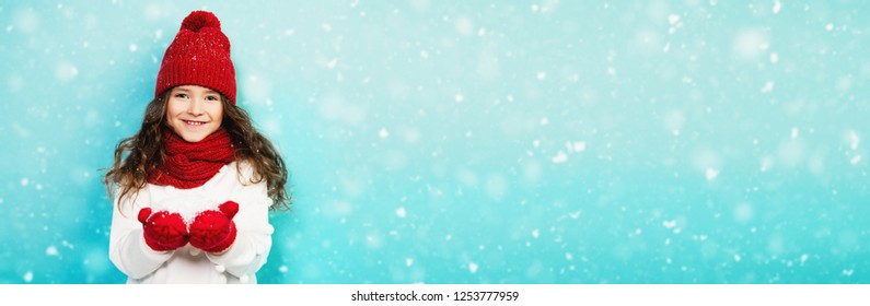 A portrait of a pretty young girl wearing a hat, a sweater, a scarf and mittens, blowing on the snow in her palms. Winter fashion for kids, beauty.