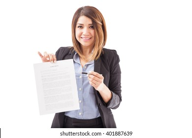 Portrait of a pretty young Hispanic brunette in a suit holding a contract ready to sign on a white background