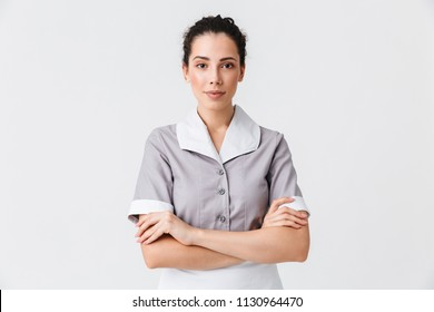 Portrait of a pretty young housemaid dressed in uniform standing with arms folded isolated over white background