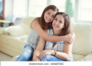 Portrait of pretty young mother with her adorable teenager daughter