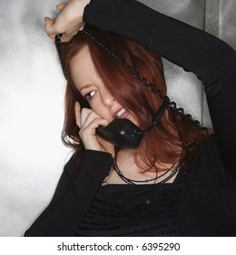 Portrait of pretty young redhead woman holding telephone receiver to ear with cord wrapped around head smiling.