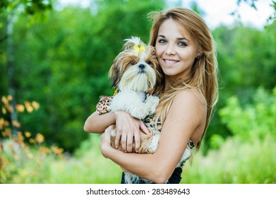 Portrait of pretty, young, smiling woman holding small fluffy dog, against background of summer green park
