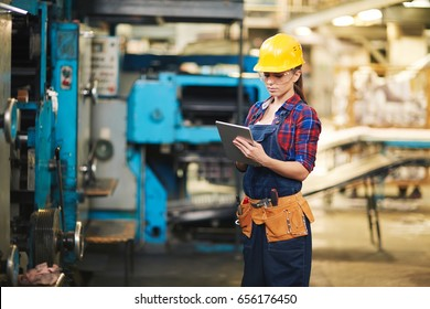 Portrait of pretty young technician wearing denim overall using digital tablet while carrying out inspection in production department of modern plant