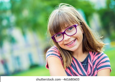Portrait of a pretty young teen girl with dental braces and glasses.