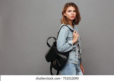 Portrait of a pretty young teenage girl dressed in denim jacket holding backpack and looking at camera isolated over gray background