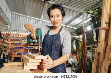 Portrait of pretty young Vietnamese carpenter using electric screwdriver when making furnuture at woodwork studio