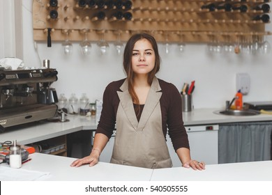 Portrait of pretty young waitress standingin cafeteria behind the counter
