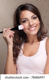 Portrait of pretty young woman applying cosmetic paint brush