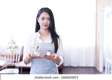 Portrait pretty young woman Asian waiter carrying plates with icecream set at the restaurant.Waitress is serving coffee in the coffee shop.