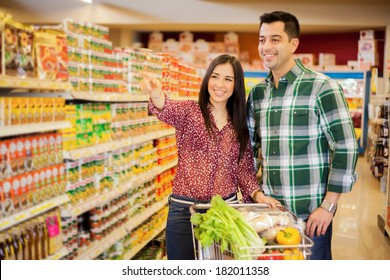 Portrait of a pretty young woman asking her partner to go some place in a supermarket