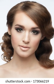Portrait of a pretty young woman with a beautiful hairstyle and makeup. Girl with wavy hair and smoky eyes