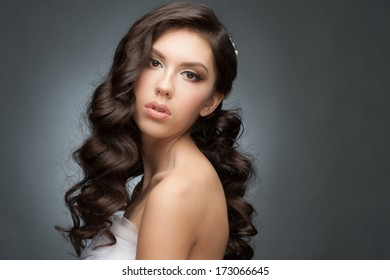 Portrait of a pretty young woman with a beautiful bridal hairstyle and makeup. Brunette with long wavy hair