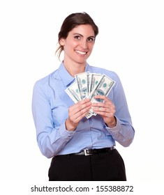 Portrait of a pretty young woman in blue blouse smiling, holding dollar currency, on isolated white background.