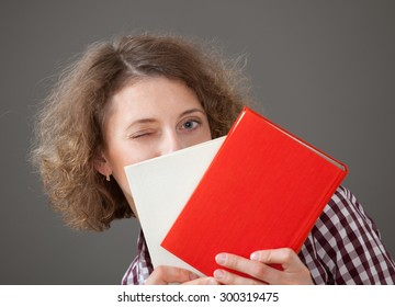 Portrait of a pretty young woman with books, gray background