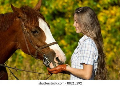 portrait of a pretty young woman with a browne horse