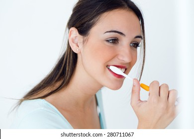 Portrait of pretty young woman brushing her teeth.