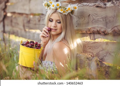 portrait of pretty young woman in chamomile wreath with bucket of cherries outdoor