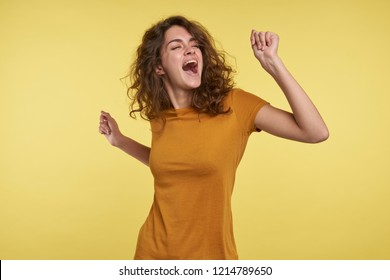 A portrait of pretty young woman with curly hair dancing and singing isolated over yellow background