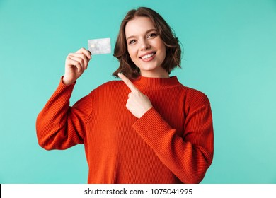 Portrait of a pretty young woman dressed in sweater pointing finger at credit card isolated over blue background