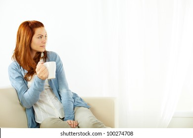 Portrait of a pretty young woman drinking a caffee cup and resting at sofa