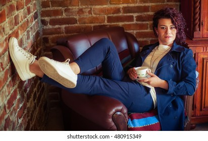 Portrait of pretty young woman drinking coffee in the room