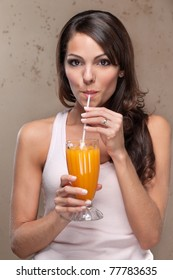 Portrait of pretty young woman drinking orange juice