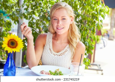 Portrait of pretty young woman eating tuna salad at restaurant