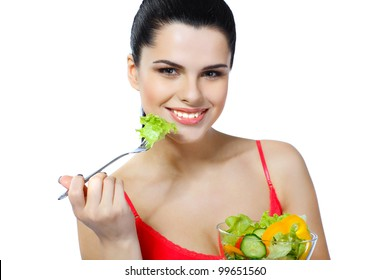 Portrait of a pretty young woman eating vegetable salad isolated on  a white background
