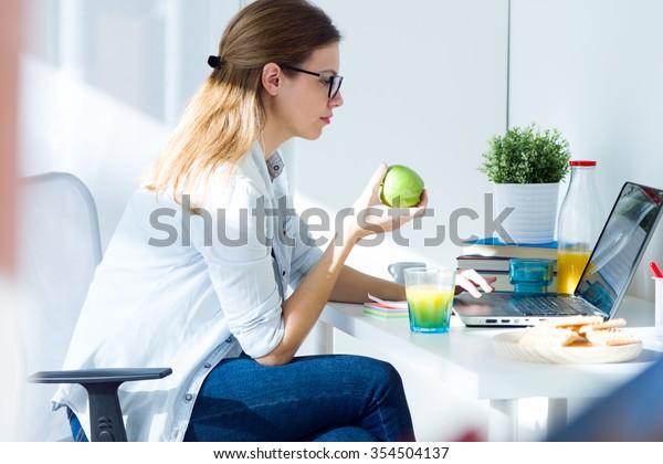 Porträt einer hübschen jungen Frau, die einen Apfel isst und zu Hause arbeitet.