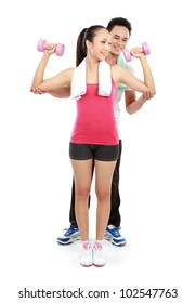 Portrait of pretty young woman with fitness instructor using dumbbells during exercising