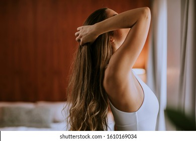 Portrait of pretty young woman flinging long brown hair into air in the room by the window