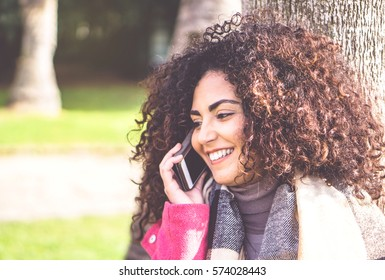 Portrait of pretty young woman having a phone call conversation with mobile smartphone while standing relaxed in peaceful place - Attractive female brunette with curly hair talking on cell telephone