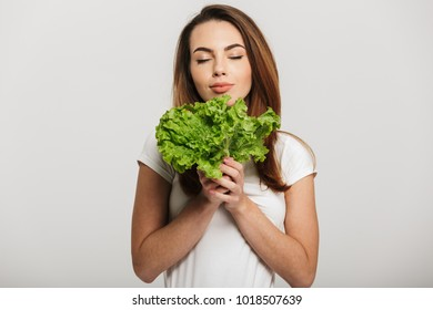 Portrait of a pretty young woman holding lettuce isolated over white background
