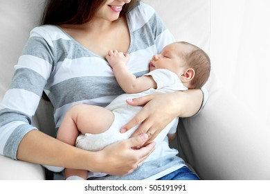 Portrait of pretty young woman holding sleeping baby at home