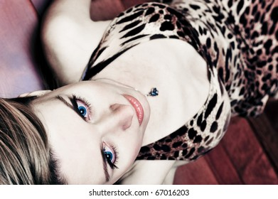 Portrait of pretty young woman laying on stairs at home and posing