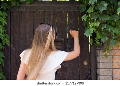 Portrait of pretty young woman with long hair knocking on doorway. Beautiful blonde female standing outdoors near house. People rest and lifestyle concept