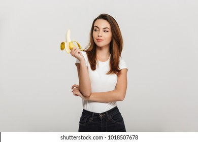 Portrait of a pretty young woman looking at banana isolated over white background