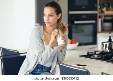 Portrait of pretty young woman looking to sideways while eating yogurt in the kitchen at home.