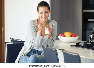 Portrait of pretty young woman looking at camera while eating yogurt in the kitchen at home.