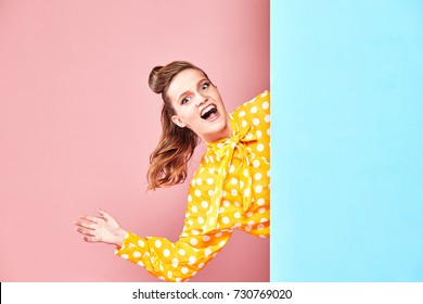 Portrait of pretty young woman model wearing yellow blouse with white polka-dot, blue skirt in pin-up style, posing and looking happy in studio with blue and pink background