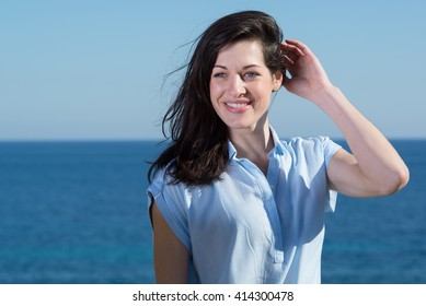 Portrait of pretty young woman on sunny day, with sea behind