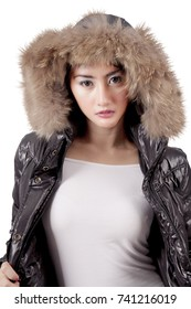 Portrait of a pretty young woman posing in the studio while wearing winter warm clothes with fur hood