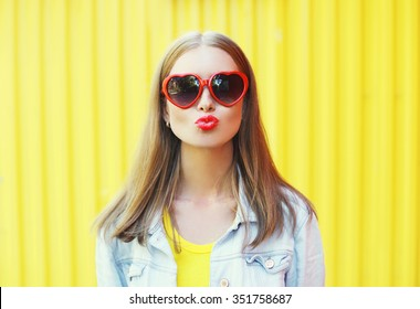 Portrait pretty young woman in red sunglasses blowing lips kiss over colorful yellow background