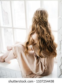 Portrait of pretty young woman sitting at the window with beautiful hairstyle decorated by stylish gold hair accessory