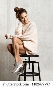 Portrait of pretty young woman sitting on chair dressed in comfy sweater. Beautiful smiling girl feeling comfortable posing in studio on beige background. Winter and beauty concept
