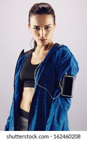 Portrait of pretty young woman in sportswear listening to music with mobile phone on armband. Beautiful young female athlete standing against grey background
