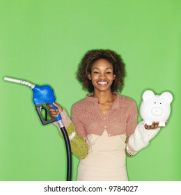 Portrait of pretty young woman standing against green background holding gasoline pump nozzle and piggybank.