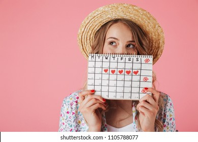 Portrait of a pretty young woman in straw hat holding women's period calendar and looking away isolated over pink background